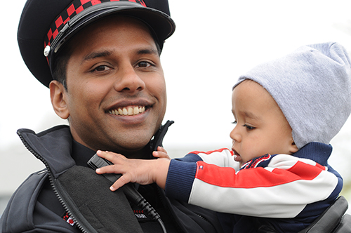 A male Auxiliary officer holds a toddler in his arms