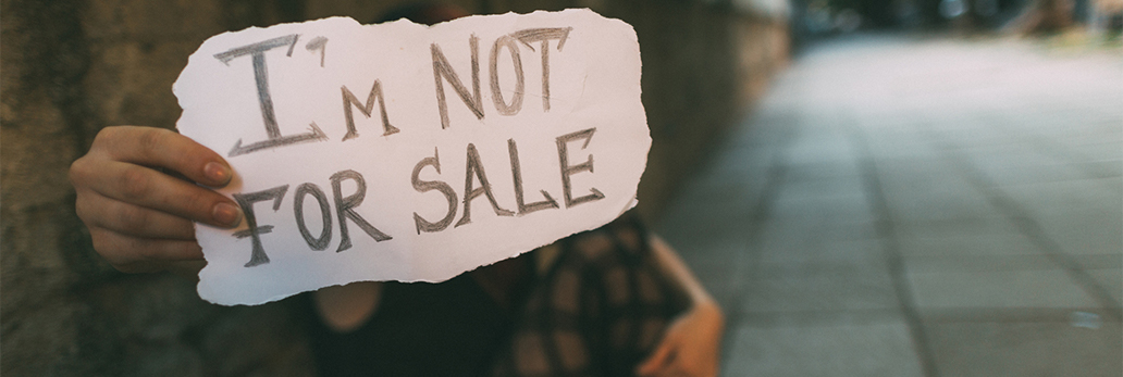 "A girl holds her hand forward, on which is written the words ""I'm not for sale."""